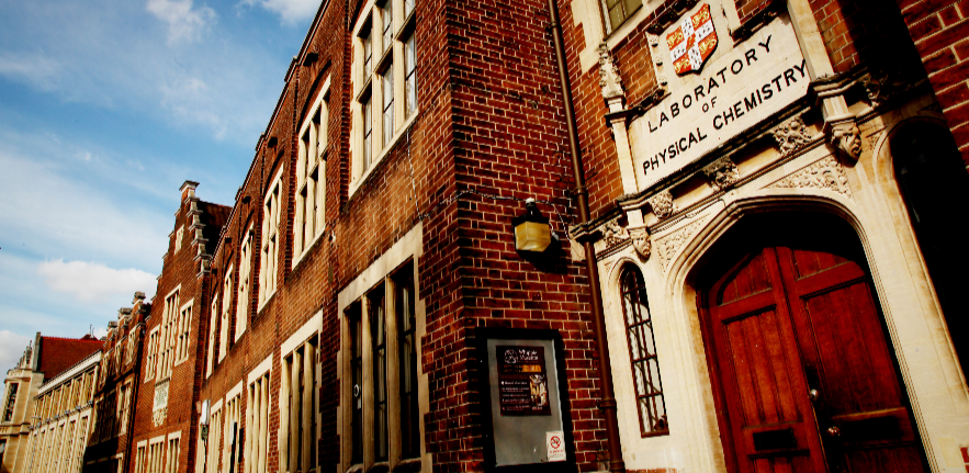 """Long brick building frontage on a sunny day. A large wooden door is on the right, with the University of Cambridge's crest and the words """"deparment of physical chemistry"""" above it."""
