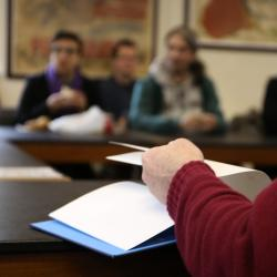 Soft focus view of a seminar in progress, with a person in a patterned jumper flipping pages of a notebook in the foreground.