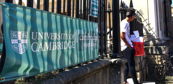 """Teal banner reading """"University of Cambridge"""" and """"Cambridge open days"""" attached to metal railings"""